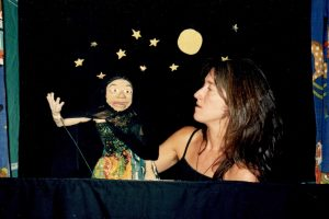 Puppeteer with an old woman rod-puppet